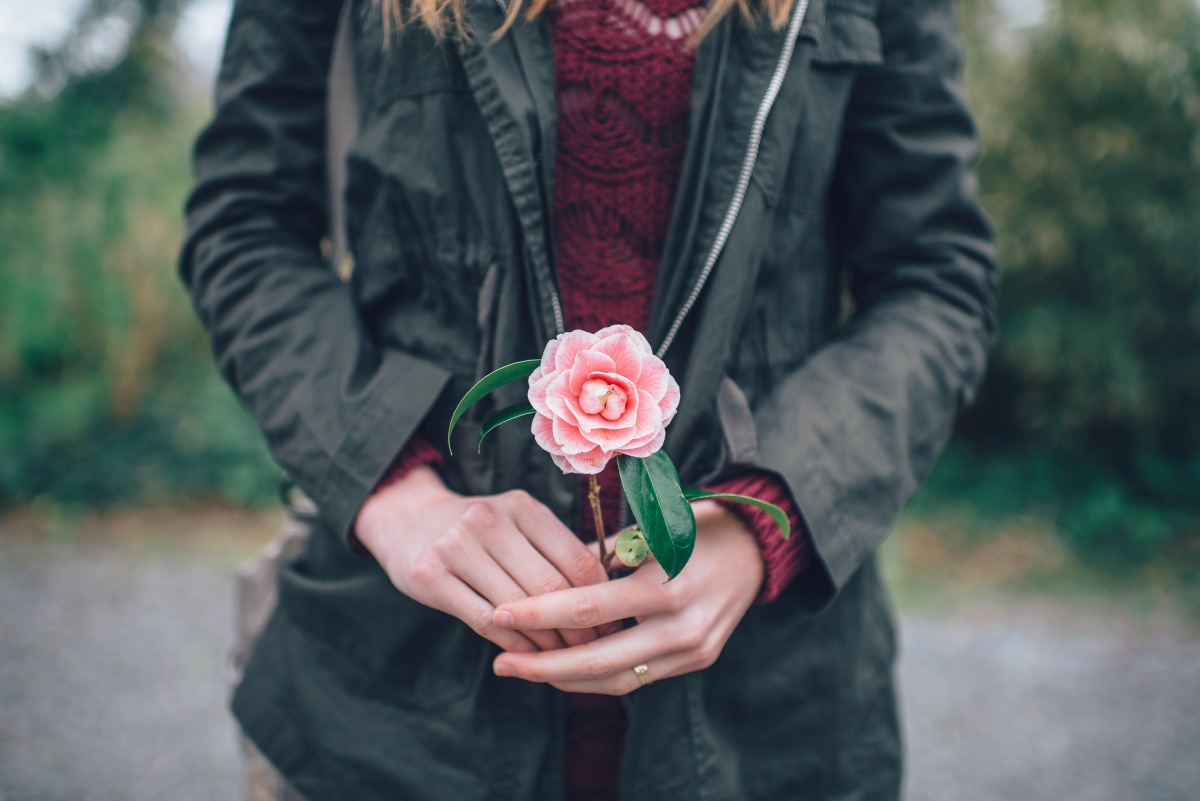 Woman holding pink flower